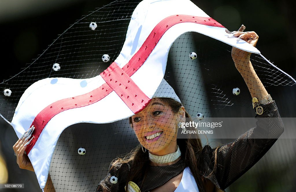 A racegoer poses for photographers with an England football themed hat ahead of the second day's horse racing at Royal Ascot, in Berkshire, west of London, on June 16, 2010. The five-day meeting is one of the highlights of the horse racing calendar. Horse racing has been held at the famous Berkshire course since 1711 and tradition is a hallmark of the meeting. Top hats and tails remain compulsory in parts of the course while a daily procession of horse-drawn carriages brings the Queen to the course.
