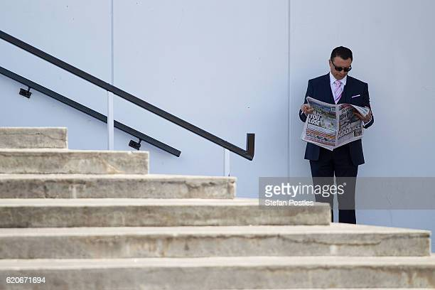 A racegoer reads the newspaper on Crown Oaks Day at Flemington Racecourse on November 3 2016 in Melbourne Australia