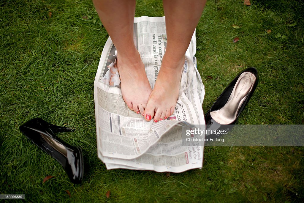A racegoer rests her feet on a newspaper on the opening day of the Grand National Festival at Aintree Racecourse on April 3, 2014 in Aintree, England. The three days of racing attracts thousands of racegoers and fans from across the world. The meeting culminates with millions of pounds being wagered on the runners taking part in Europe's richest jump race, the Grand National.