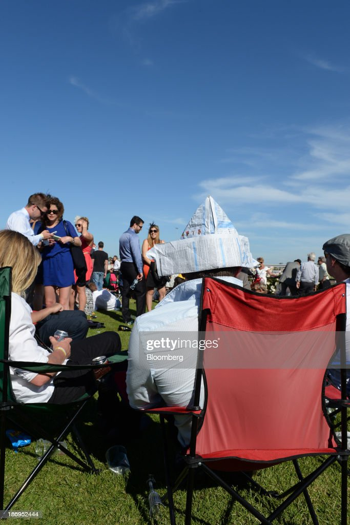 A racegoer sits with a paper hat made from a form guide during Melbourne Cup Day at Flemington Racecourse in Melbourne, Australia, on Tuesday, Nov. 5, 2013. The Melbourne Cup, marketed as the race that stops the nation, is Australias premier thoroughbred horse racing event. Photographer: Carla Gottgens/Bloomberg via Getty Images