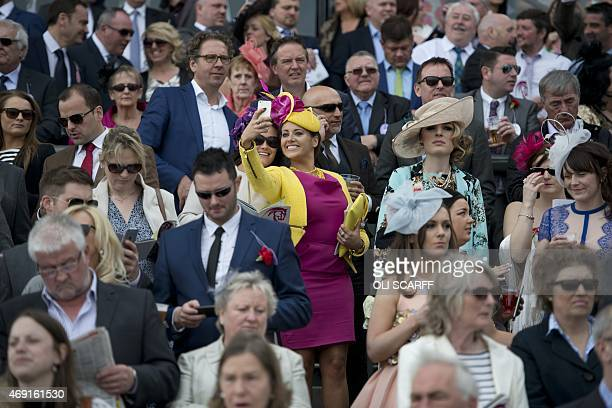 A racegoer takes a 'selfie' from a grandstand on 'Ladies Day' of the Grand National Festival horse race meeting at Aintree Racecourse in Liverpool...