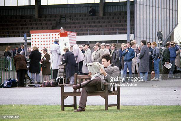 A racegoer users his newspaper to look up the latest odds as punters queue to place bets in the background