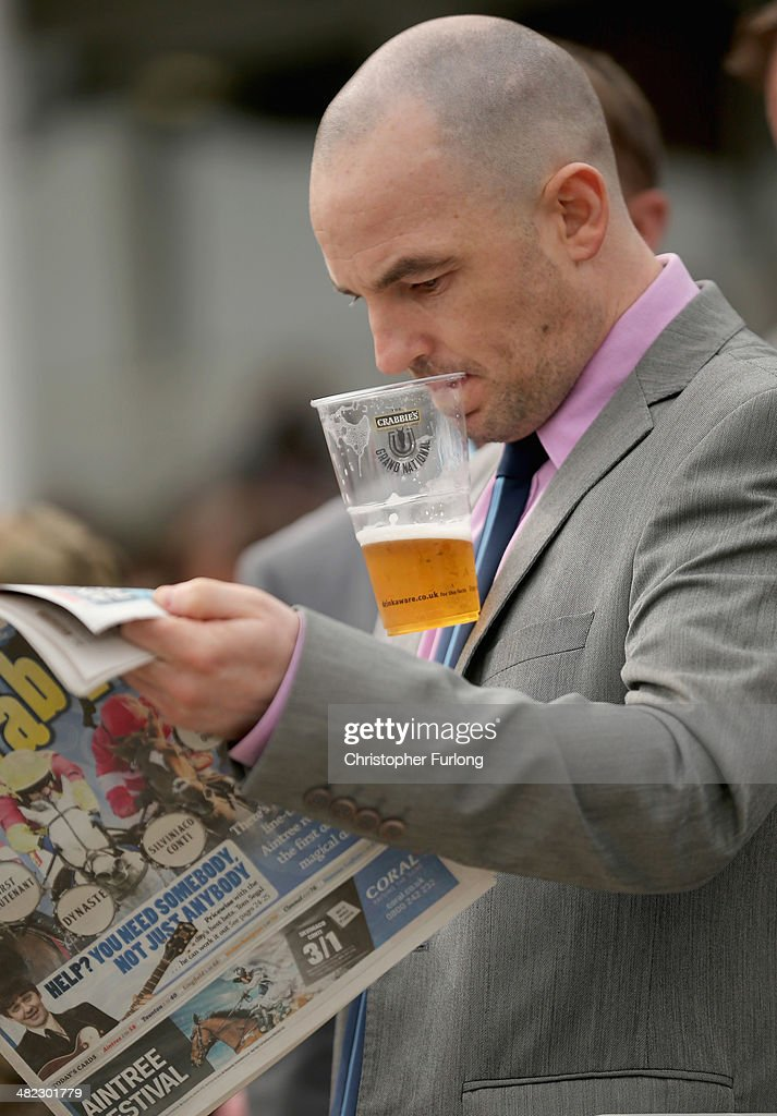 A racegoer uses his teeth to hold his beer as he checks the form in a newspaper on the opening day of the Grand National Festival at Aintree Racecourse on April 3, 2014 in Aintree, England. The three days of racing attracts thousands of racegoers and fans from across the world. The meeting culminates with millions of pounds being wagered on the runners taking part in Europe's richest jump race, the Grand National.