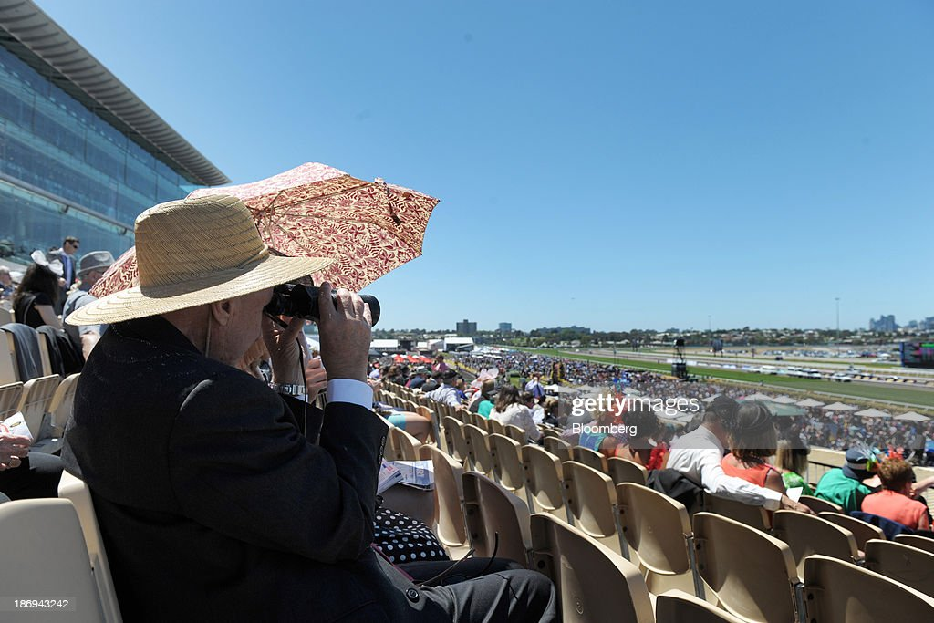 A racegoer watches a race through binoculars from the Hill Stand on Melbourne Cup Day at Flemington Racecourse in Melbourne, Australia, on Tuesday, Nov. 5, 2013. The Melbourne Cup, marketed as the race that stops the nation, is Australias premier thoroughbred horse racing event. Photographer: Carla Gottgens/Bloomberg via Getty Images