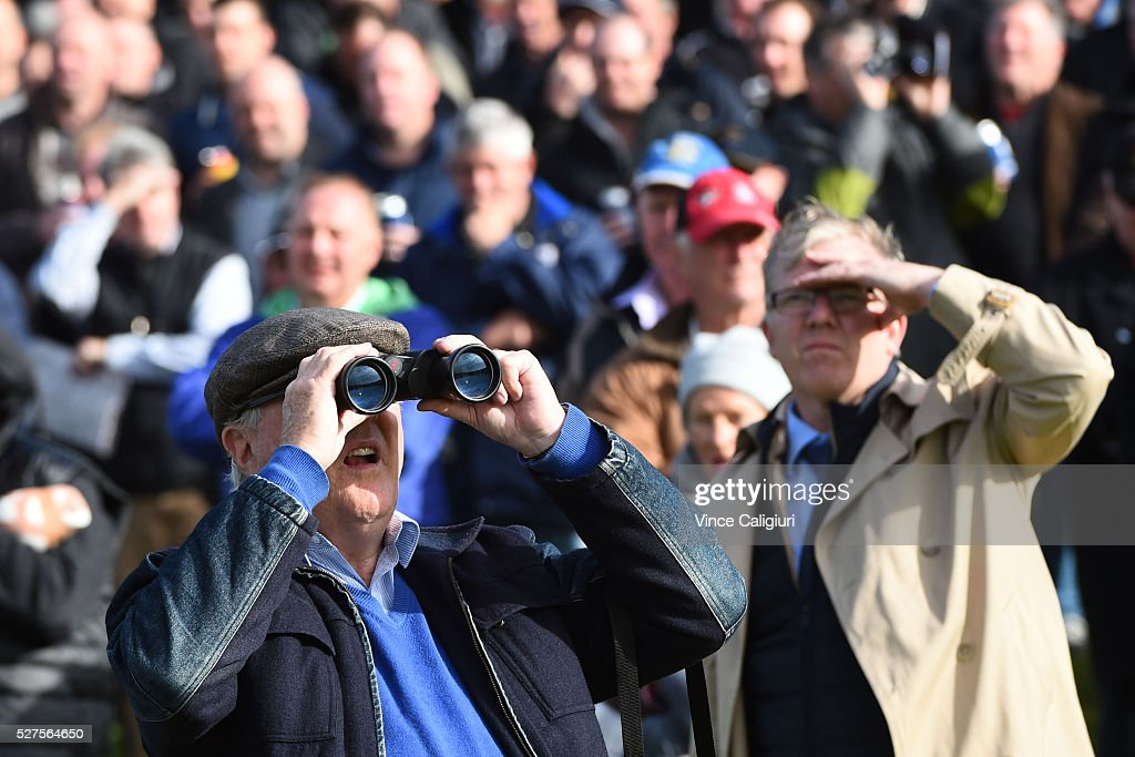 A racegoer watches the races through binoculars during Brierly Day at Warrnambool Race Club on May 3, 2016 in Warrnambool, Australia.