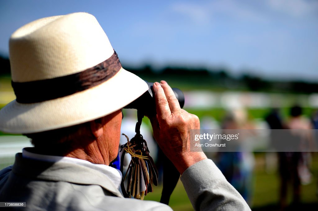 A racegoer watching through binoculars at Leicester racecourse on July 18, 2013 in Leicester, England.