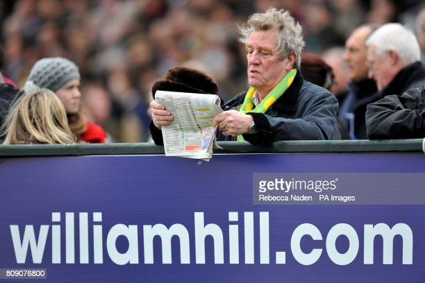 A racegoer wearing a Kauto Star scarf inspects the Racing Post newspaper for tips