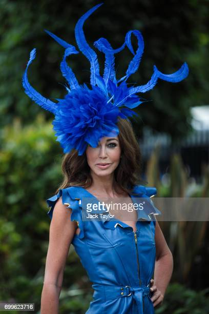 A racegoer wearing an elaborate blue hat poses for a photograph on day 3 of Royal Ascot at Ascot Racecourse on June 22 2017 in Ascot England The...