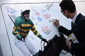 A racegoer writes a message to jockey AP McCoy on the opening day of the Grand National Festival horse race meeting at Aintree Racecourse in...
