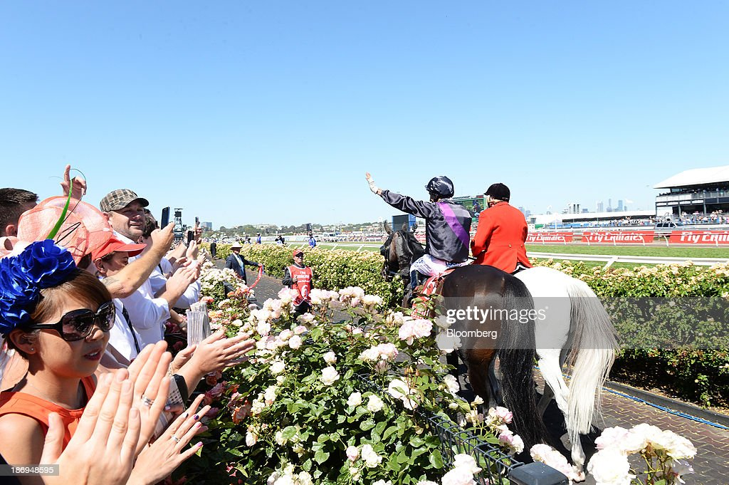 Racegoers applaud jockey Damien Oliver, left, as he rides Fiorente back to the yard after winning race 7 The Emirates Melbourne Cup during Melbourne Cup Day at Flemington Racecourse in Melbourne, Australia, on Tuesday, Nov. 5, 2013. The Melbourne Cup, marketed as the race that stops the nation, is Australias premier thoroughbred horse racing event. Photographer: Carla Gottgens/Bloomberg via Getty Images