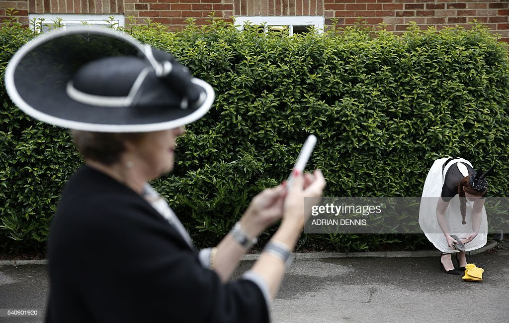 Racegoers arrive to attend the fourth day of Royal Ascot in Berkshire west of London on June 17 2016 The fiveday meeting is one of the highlights of...