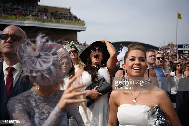 Racegoers attend 'Ladies Day' of the Grand National Festival horse race meeting at Aintree Racecourse in Liverpool Northern England on April 10 2015...