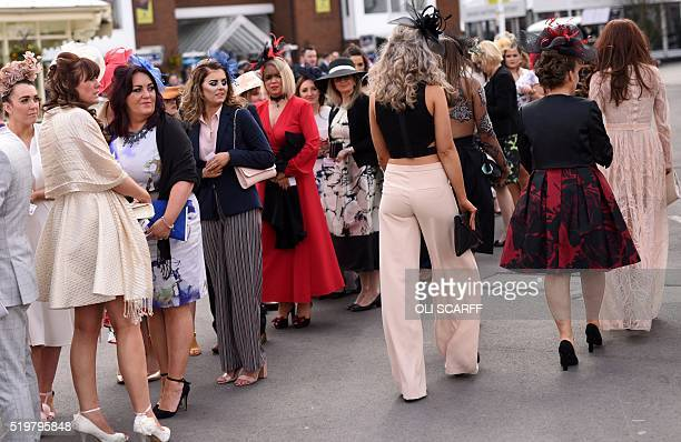 Racegoers attend Ladies Day the second day of the Grand National Festival horse race meeting at Aintree Racecourse in Liverpool northern England on...