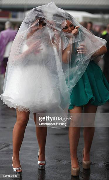 Racegoers brave the rain as they refuse to let it spoil the occasion of Ladies Day at the Aintree Grand National meeting on April 13 2012 in Aintree...
