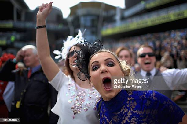Racegoers celebrate a win and enjoy the atmosphere of Ladies Day the second day of the Aintree Grand National Festival meeting on April 8 2016 in...