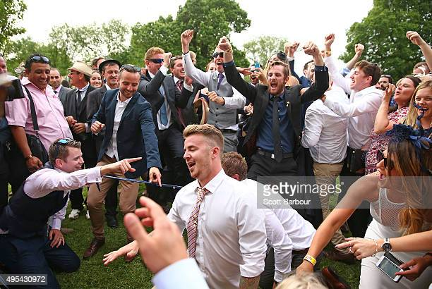 racegoers celebrate as a man attempts to bend backwards between two racegoers who have their ties tied together as racegoers play a game of Limbo...