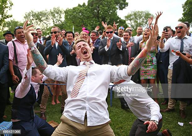 Racegoers celebrate as a man successfully bends backwards between two racegoers who have their ties tied together as racegoers play a game of Limbo...