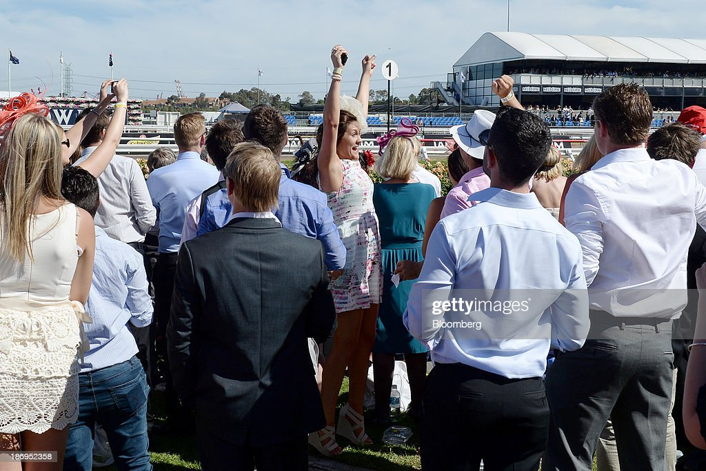 Racegoers celebrate during Melbourne Cup Day at Flemington Racecourse in Melbourne, Australia, on Tuesday, Nov. 5, 2013. The Melbourne Cup, marketed as the race that stops the nation, is Australias premier thoroughbred horse racing event. Photographer: Carla Gottgens/Bloomberg via Getty Images