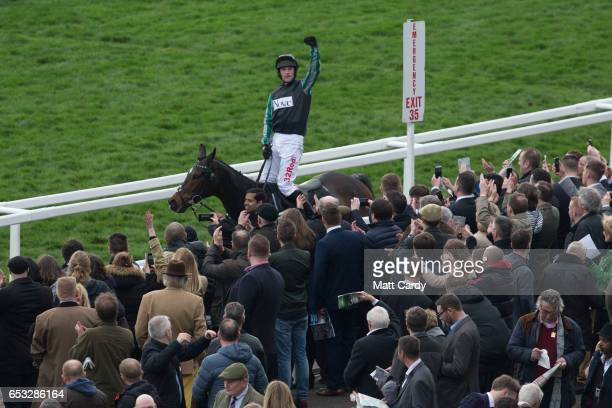 Racegoers cheer as the winner of the second race Altior ridden by Nico de Boinville passes them as they watch the racing at the Cheltenham Racecourse...