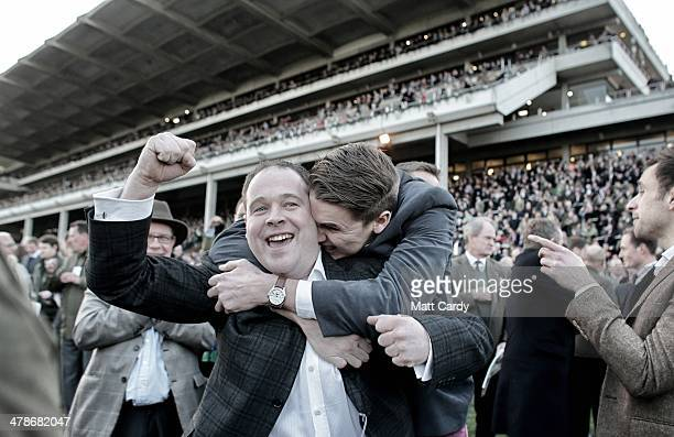 Racegoers cheer as they celebrate a win in the last race of the day on the first day of the Cheltenham Festival on March 11 2014 in Cheltenham...