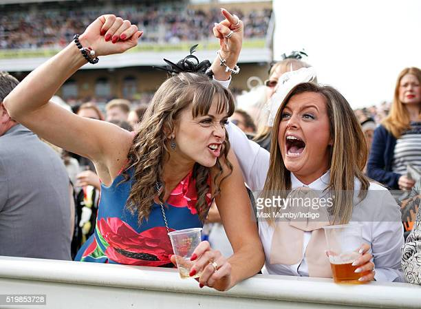 Racegoers cheer as they watch the racing on day 2 'Ladies Day' of the Crabbie's Grand National Festival at Aintree Racecourse on April 8 2016 in...