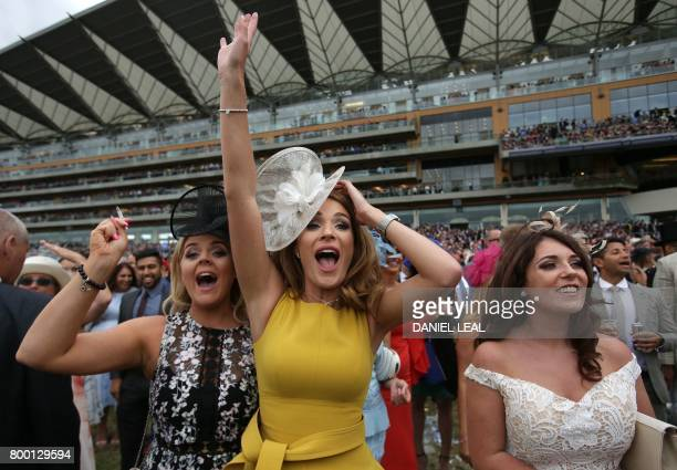 Racegoers cheer for their backed horse as it runs but fails to win as they attend the fourth day of the Royal Ascot horse racing meet in Ascot west...