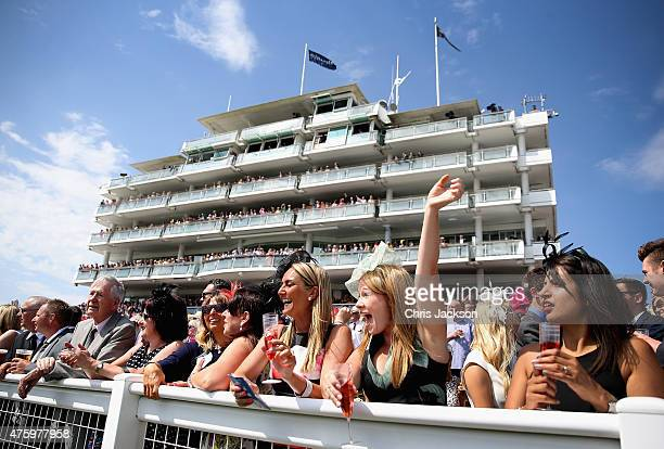 Racegoers cheer on the horses during Ladies Day at the Investec Derby Festival on June 5 2015 in Epsom England