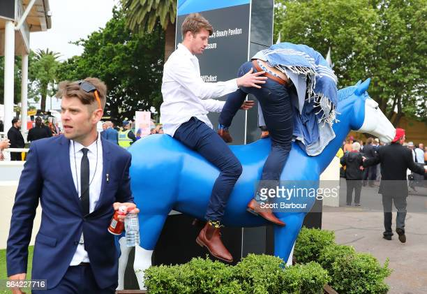 Racegoers climb onto a statue of a horse during Caulfield Cup Day at Caulfield Racecourse on October 21 2017 in Melbourne Australia