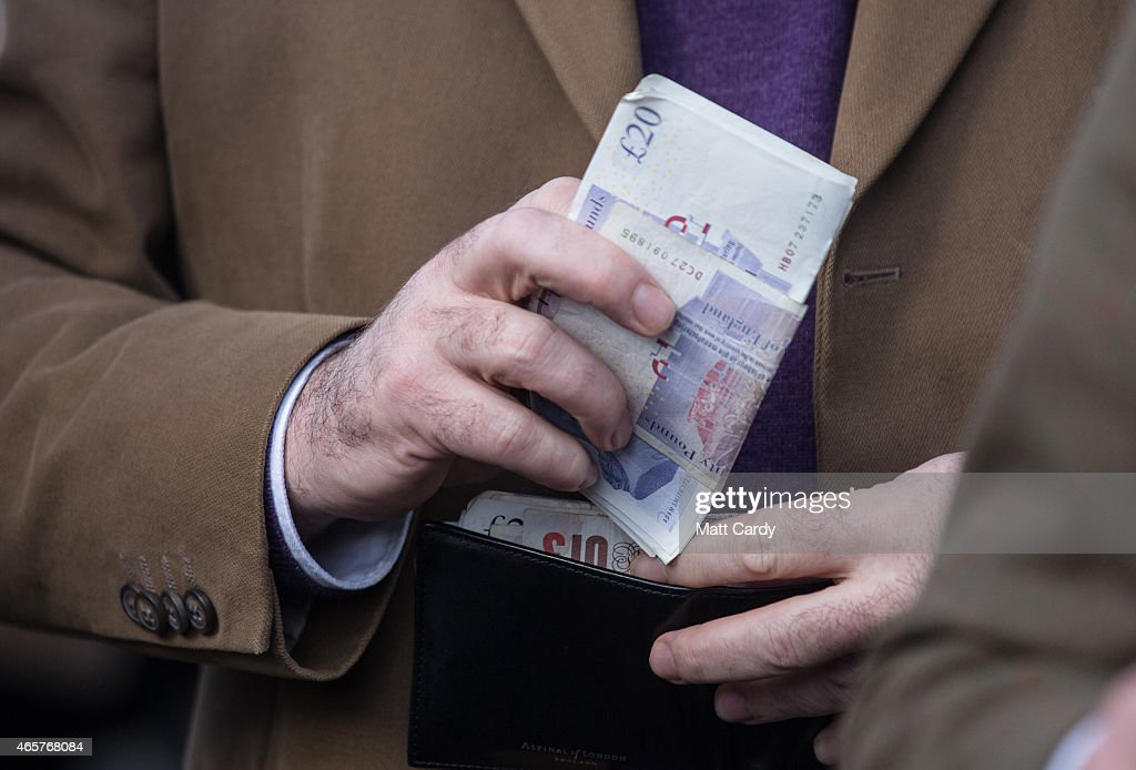 A racegoers counts his cash at Cheltenham Racecourse on the first day of the Cheltenham Festival on March 10 2015 in Cheltenham England Thousands of...
