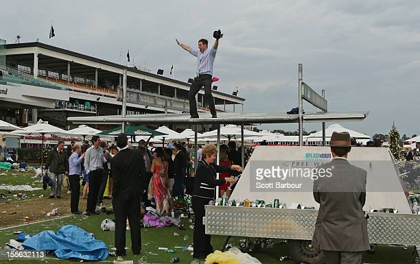 A racegoers dances on the roof of a shelter after the Melbourne Cup at Flemington Racecourse on November 6 2012 in Melbourne Australia