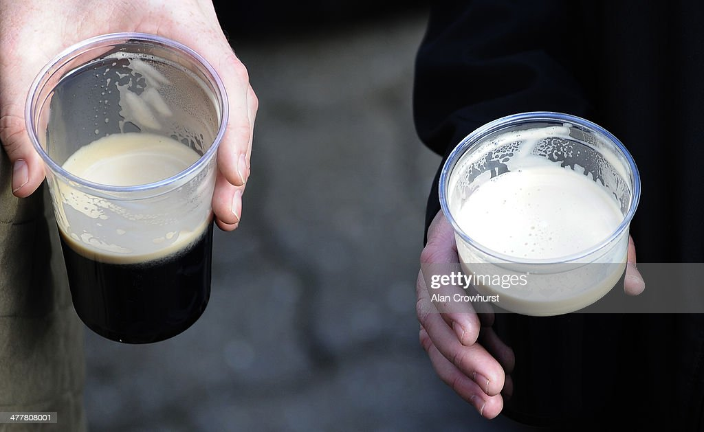 Racegoers drink Guinness at Cheltenham racecourse on March 11 2014 in Cheltenham England