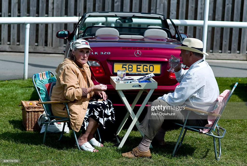 Racegoers enjoy a picnic by their vehicle before racing at Chester racecourse on May 4, 2016 in Chester, England.