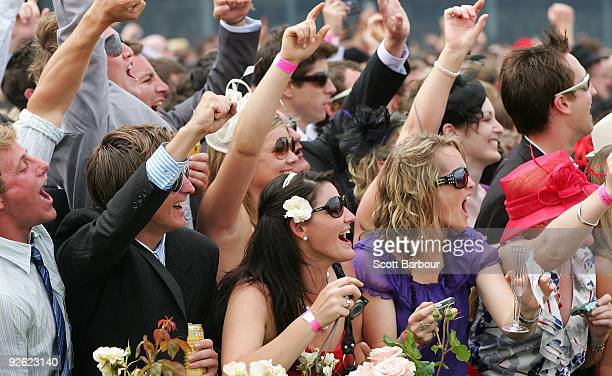 Racegoers gesture as they watch horses run in the Emirates Melbourne Cup during the 2009 Melbourne Cup Day meeting at Flemington Racecourse on...