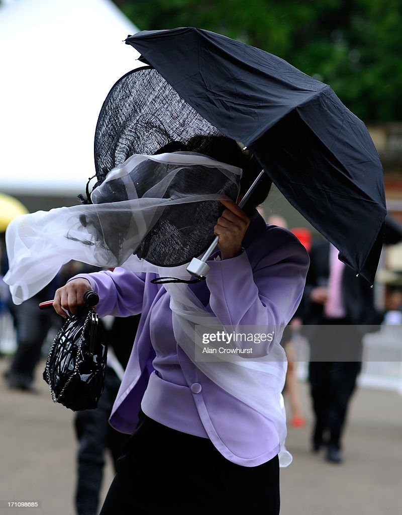 Racegoers hold onto their hats as they arrive during day five of Royal Ascot at Ascot Racecourse on June 22, 2013 in Ascot, England.