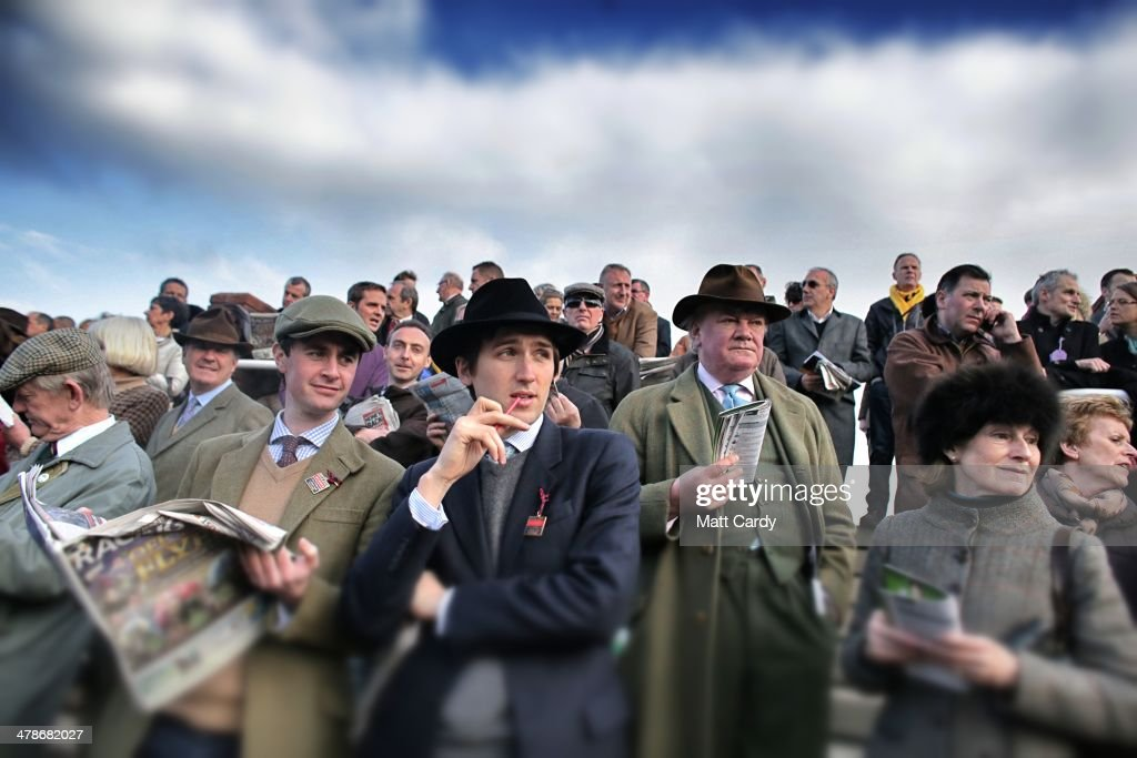 Racegoers look at horses outside the weighing room on the first day of the Cheltenham Festival on March 11, 2014 in Cheltenham, England. Thousands of racing enthusiasts are expected at the four-day festival, which starts today with the festival's Champion Day and is seen as many as the highlight of the jump racing calendar.
