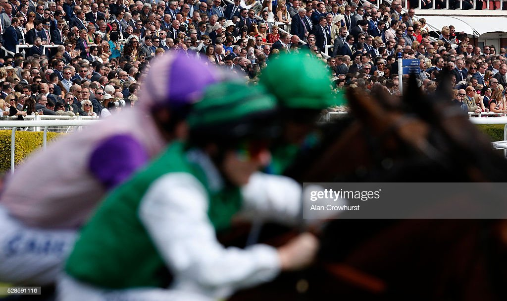 Racegoers look on as runners break from the stalls at Chester racecourse on May 6, 2016 in Chester, England.
