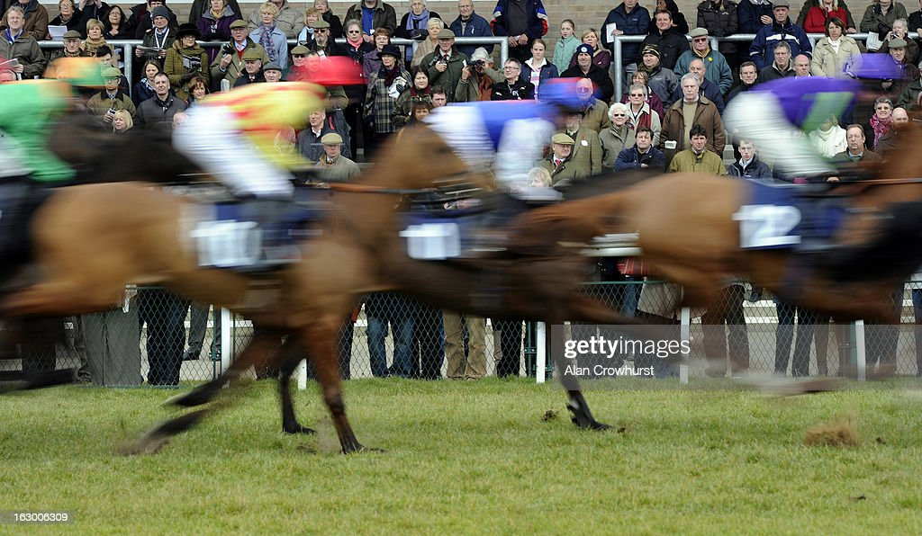 Racegoers look on as the runners pass at Huntingdon racecourse on March 03, 2013 in Huntingdon, England.