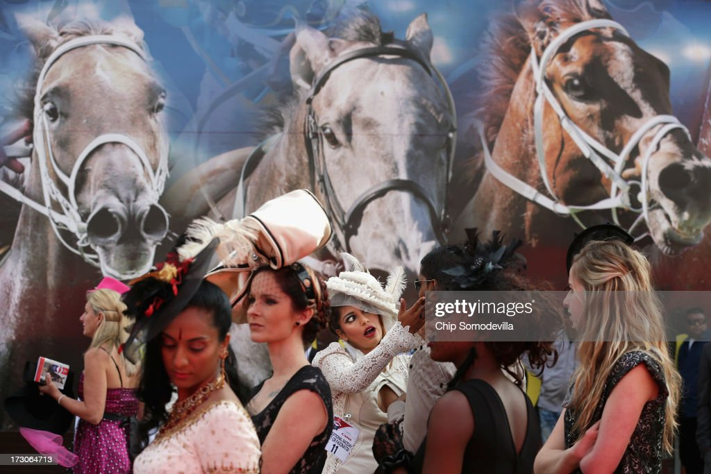 Racegoers participate in a fashion competition during the Durban July horse races July 6, 2013 in Durban, South Africa. South Africa's premier horse racing event, the 2200-meter Durban July is held annually on the first Saturday of July since 1897 and offers a purse of 2.5 million Rand or about US $245,000.