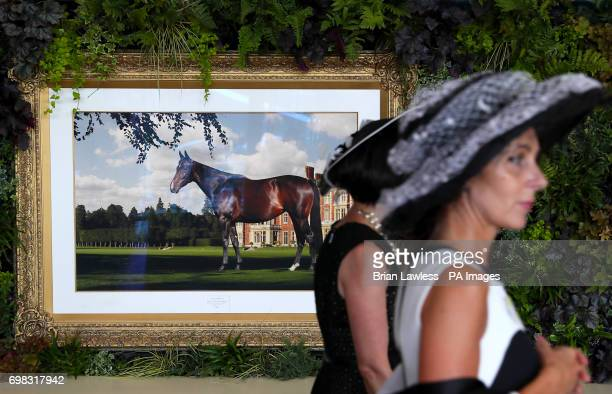 Racegoers pass by a picture of racehorse Estimate owned by Queen Elizabeth II during day one of Royal Ascot at Ascot Racecourse