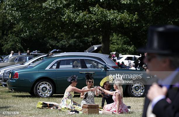 Racegoers picnic in the carpark alongside a RollsRoyce car during Ladies' day at Royal Ascot in Berkshire west of London on June 18 2015 The fiveday...