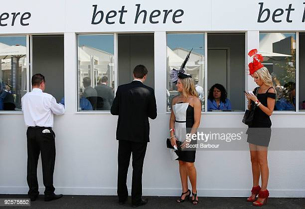 Racegoers place a bet during the AAMI Victoria Derby Day at Flemington Racecourse on October 31 2009 in Melbourne Australia