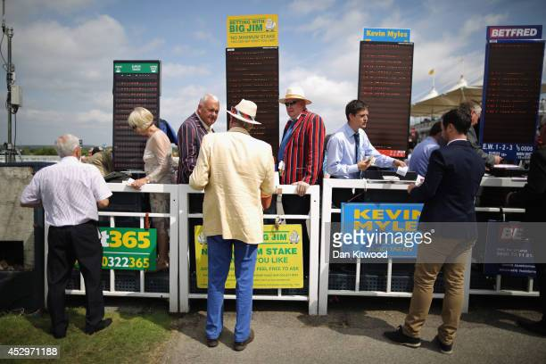 Racegoers place bets ahead of a race on Ladies Day at Goodwood Races on July 31 2014 in Chichester England Today is Ladies Day at the prestigious...