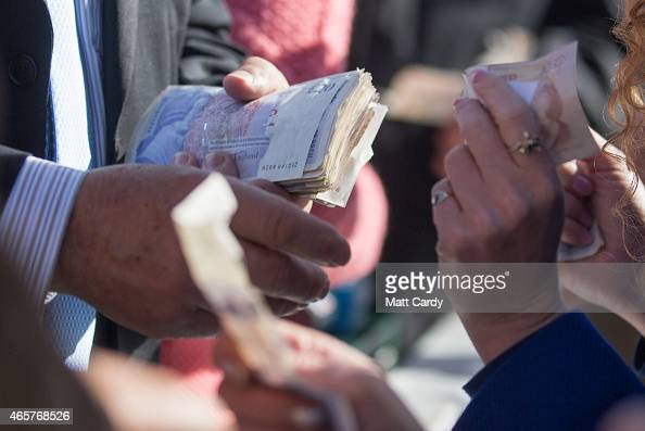 Racegoers place bets at Cheltenham Racecourse on the first day of the Cheltenham Festival on March 10 2015 in Cheltenham England Thousands of racing...