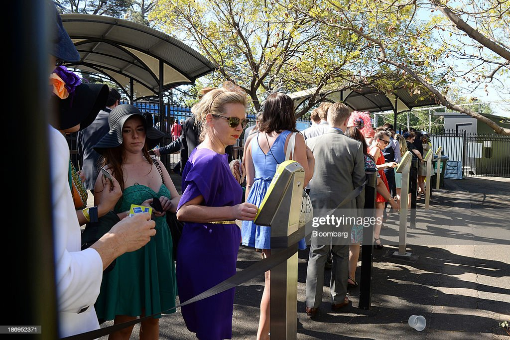 Racegoers queue to catch public transport during Melbourne Cup Day at Flemington Racecourse in Melbourne, Australia, on Tuesday, Nov. 5, 2013. The Melbourne Cup, marketed as the race that stops the nation, is Australias premier thoroughbred horse racing event. Photographer: Carla Gottgens/Bloomberg via Getty Images