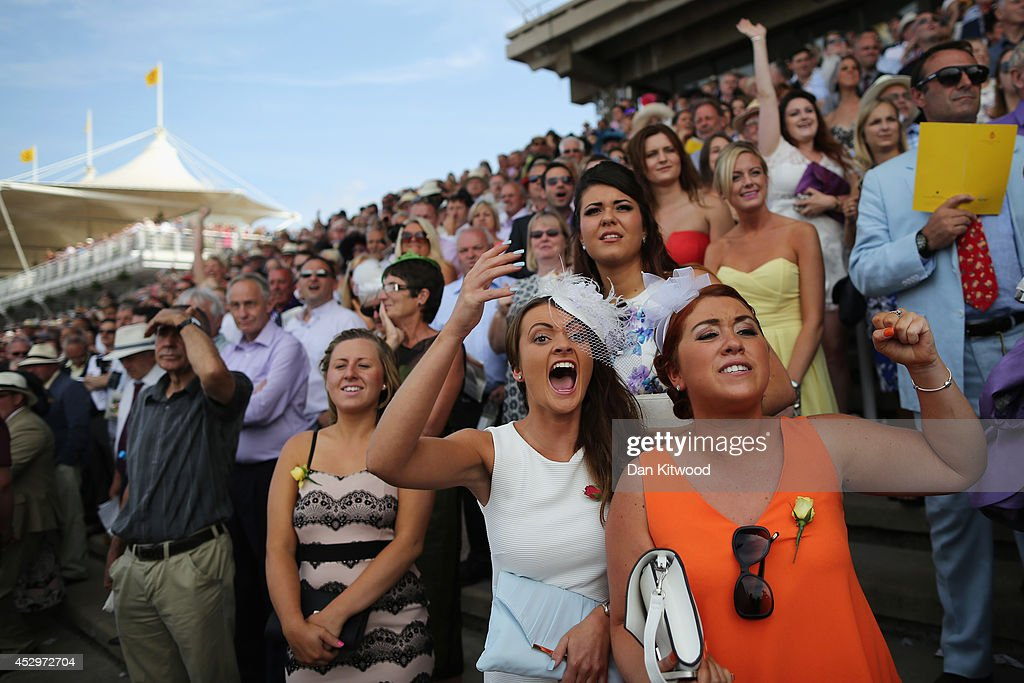 Racegoers react during a race on Ladies Day at Goodwood Races on July 31, 2014 in Chichester, England. Today is Ladies Day at the prestigious Goodwood Races.