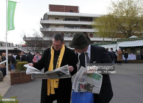 Racegoers read the racing post for tips on Centenary Day during the Cheltenham Festival