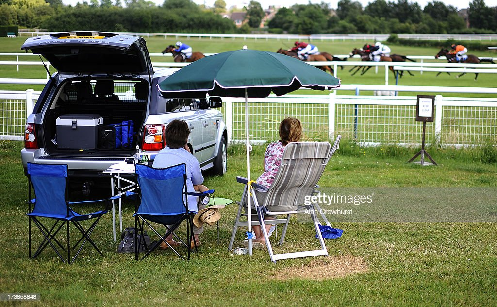 Racegoers relax during a warm day as the runners make their way to the finish at Leicester racecourse on July 18, 2013 in Leicester, England.