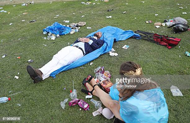 Racegoers rest amongst the rubbish as they make their way home following 2016 Melbourne Cup Day at Flemington Racecourse on November 1 2016 in...