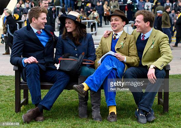 Racegoers share a laugh as they wait for a race to begin during Gold Cup day at the Cheltenham Festival at Cheltenham Racecourse on March 18 2016 in...