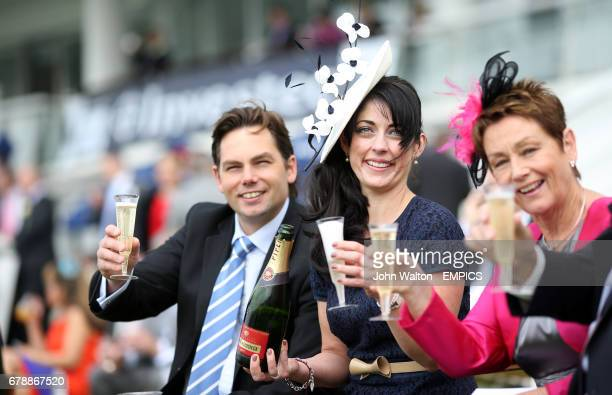 Racegoer's share a toast as they enjoy their first glass of champagne of the day